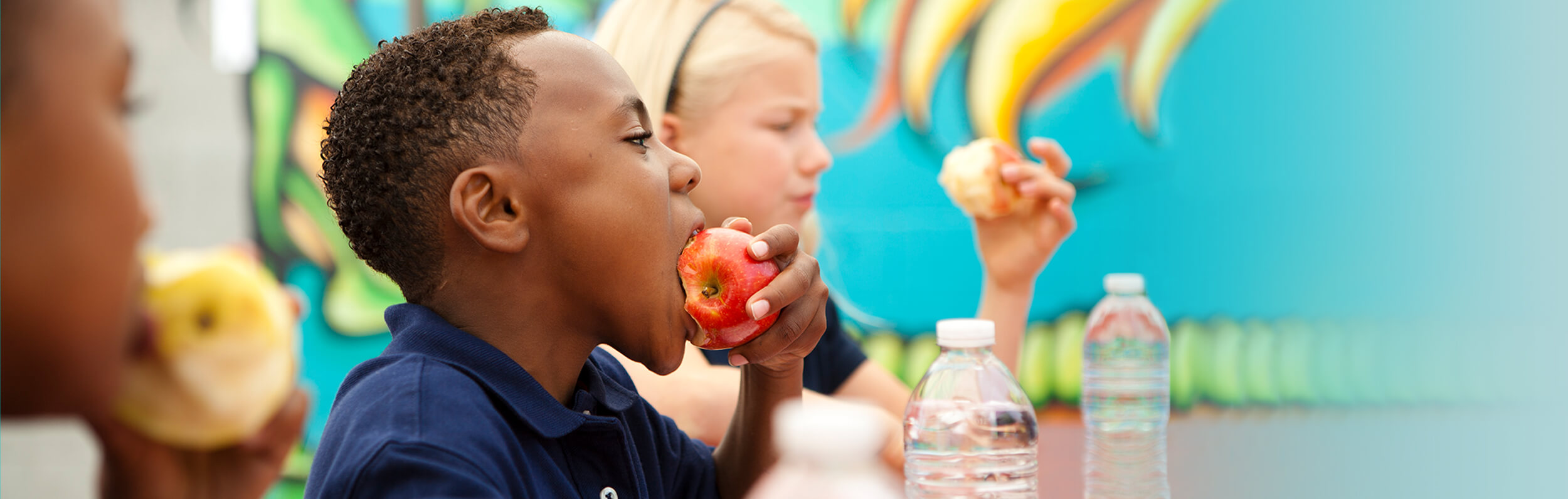 food program for daycare - children eating apples and drinking water - Novick Childcare