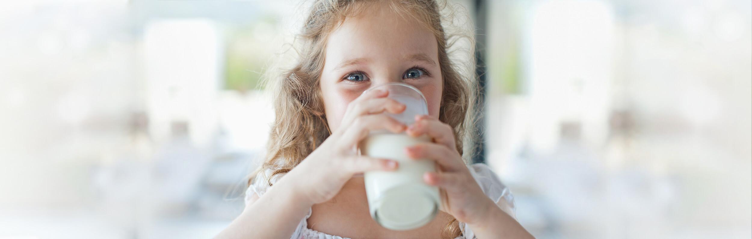 food program for daycare providers - little girl drinking milk - Novick Childcare