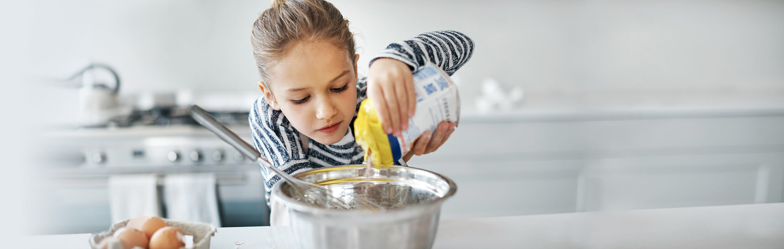 Child Care Food Program - child pouring into a mixing bowl - Novick Childcare